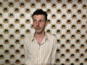 Taco Hidde Bakker, één van de volgende deelnemers aan Spiegelrefleksies, tegen een Slimtarra-behangetje van Knust