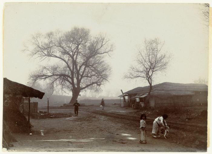 Jan Adriani: Twee kinderen spelen met een hond bij enkele huizen en twee wilgen, Pyongyang, Korea, 1907. Collectie Rijkmuseum